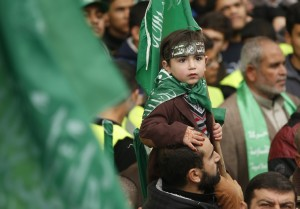 A Palestinian boy wears the headband of Hamas's armed wing as he sits on the shoulders of his father during a rally ahead of the 27th anniversary of Hamas founding, in Jabaliya in the northern Gaza Strip